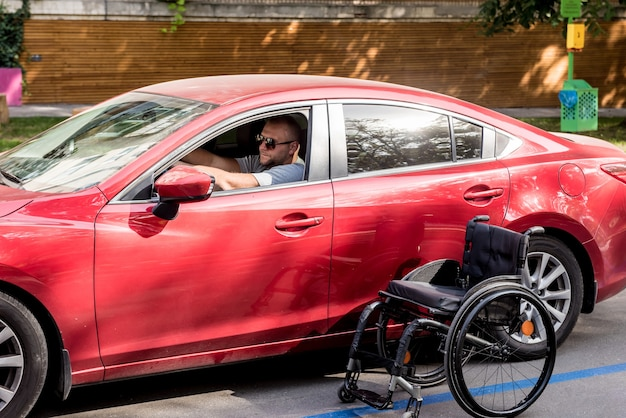 Young handicapped man on driver's seat of his car.