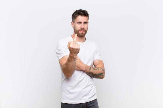 怒っている、イライラする、反抗的で攻撃的な感じの若いhandosme男、中指を反転し、フラットカラーの壁に対して反撃