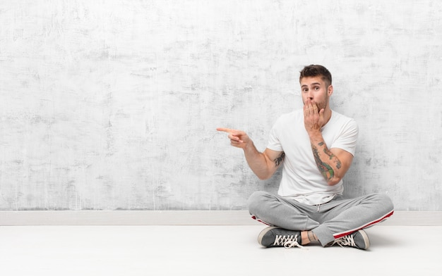 Young handosme man feeling happy, shocked and surprised, covering mouth with hand and pointing to lateral copy space against flat color wall