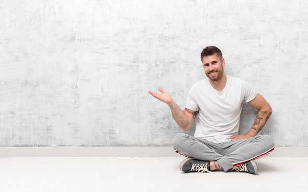 Young handosme man smiling, feeling confident, successful and happy, showing concept or idea on copy space on the side against flat color wall