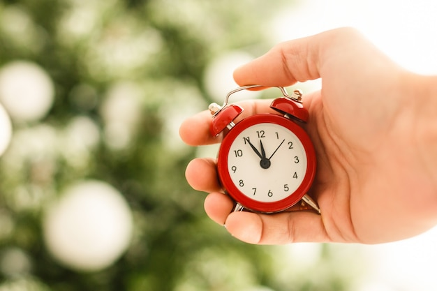 Young hands christmas alarm clock photo in old color image style