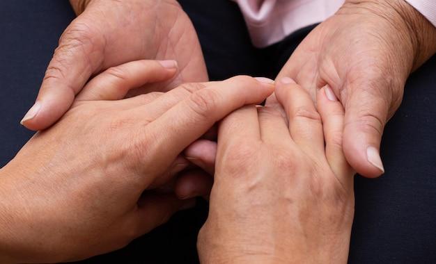 젊은 손은 늙은 손을 잡습니다. 노인 개념에 대한 지원.