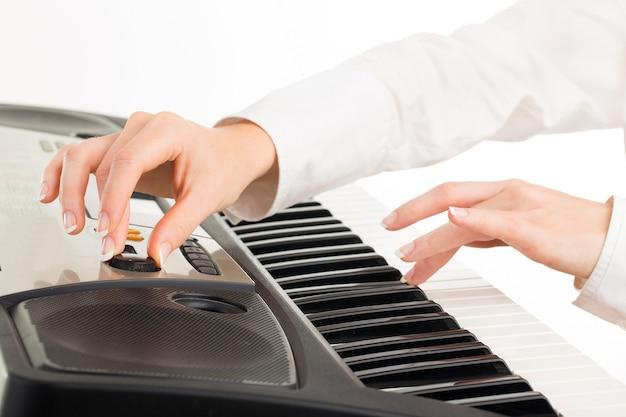 Молодые руки женщины играя синтезатор изолированные на белизне