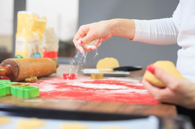 Молодые руки разбрызгивают муку на коврик для выпечки и готовят имбирное тесто
