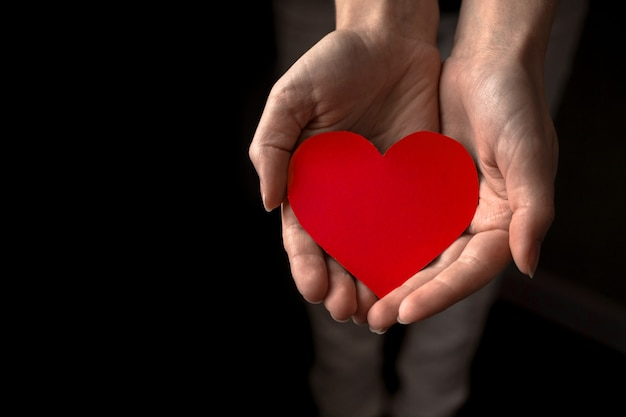 Young hands with red heart. offering help and love concept. world health and mental day background photo