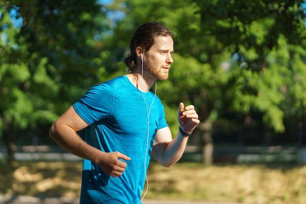 Молодой красивый активный спортсмен в синей рубашке работает в жаркий солнечный день на природе