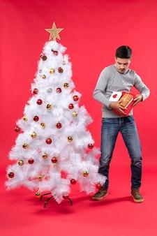 Молодой красивый взрослый в серой блузке стоит возле украшенной белой елки и открывает свои подарки