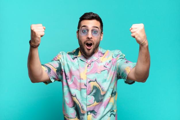 승자처럼 믿을 수없는 성공을 축하하는 젊은 잘 생긴 성인 남자, 흥분하고 행복해 보이는 말을 받아보세요!