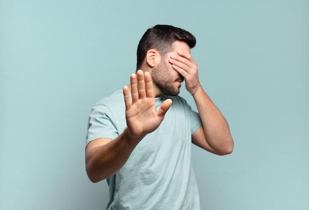 手で顔を覆い、カメラを停止するためにもう一方の手を前に置き、写真や写真を拒否する若いハンサムな大人の男