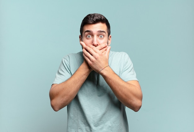 Молодой красивый взрослый мужчина прикрывает рот руками с шокированным, удивленным выражением лица, хранит секрет или говорит: ой