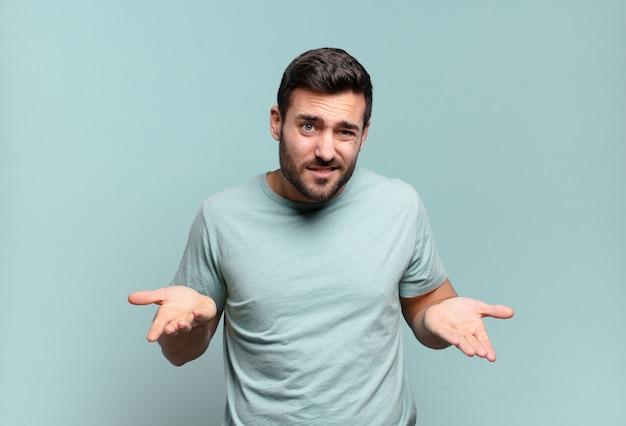 Молодой красивый взрослый мужчина чувствует себя невежественным и сбитым с толку, не уверенный, какой выбор или вариант выбрать, задаваясь вопросом