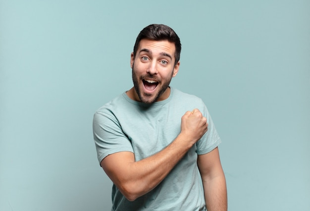 Молодой красивый взрослый мужчина чувствует себя счастливым, позитивным и успешным, мотивированным, когда сталкивается с проблемой или празднует хорошие результаты