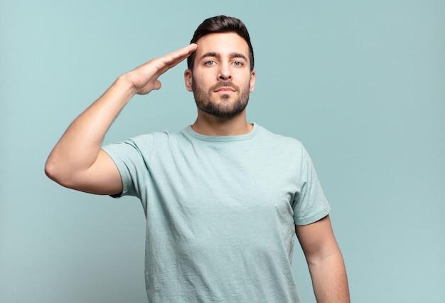 존경을 표시하는 명예와 애국의 행위에서 군사 경례와 함께 카메라를 인사하는 젊은 잘 생긴 성인 남자