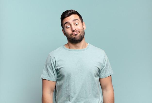 Молодой красивый взрослый мужчина выглядит глупо и смешно с глупым косоглазым выражением лица, шутит и дурачится