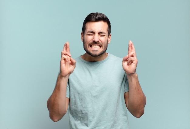 若いハンサムな大人の男は笑顔で心配そうに両指を交差させ、心配を感じ、幸運を願ったり期待したりします