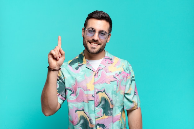 Young handsome adult man smiling cheerfully and happily, pointing upwards with one hand to copy space. holidays concept