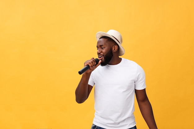 Young handsome african american boy singing emotional with microphone isolated