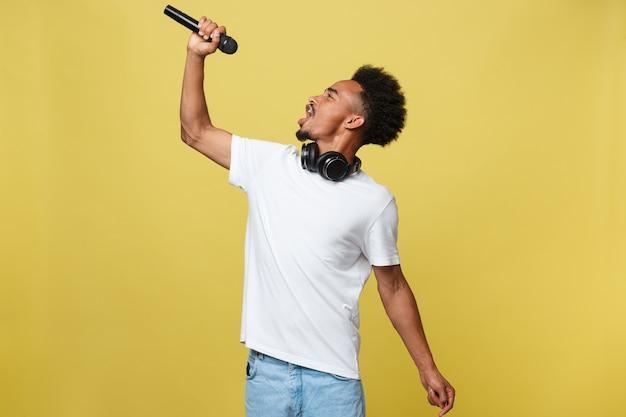 Молодой красивый афро-американский мальчик поет с микрофоном.