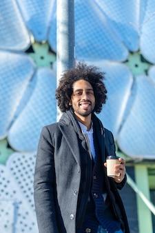 행복 한 미소 젊은 잘 생긴 아프리카 계 미국인 남자. 마을 거리에서 커피를 마시는 얼굴에 미소를 지으며 서 있습니다.