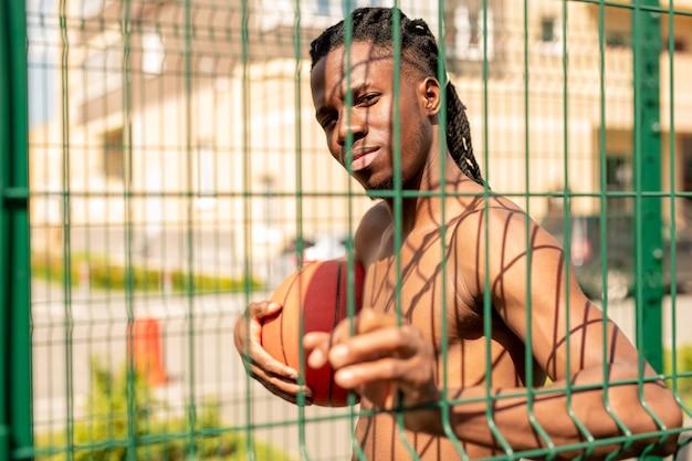 晴れた日に遊び場を取り巻くフェンスのバーを見ながらボールを保持している若いハンサムなアフリカのバスケットボール選手