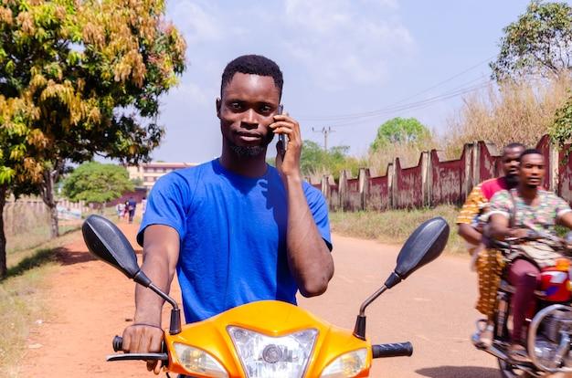 彼の顧客が到着するのを待っている間に電話をかける若いハンサムなアフリカのバイカー