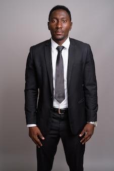 灰色の背景に若いハンサムなアフリカの実業家