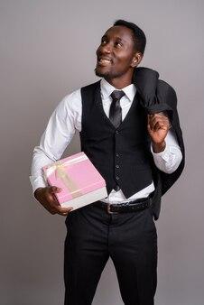 Молодой красивый африканский бизнесмен на сером фоне