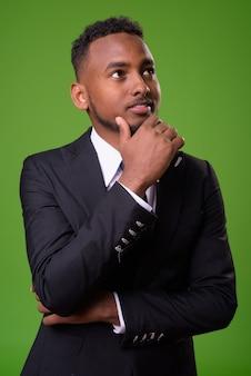 緑の背景に若いハンサムなアフリカのビジネスマン