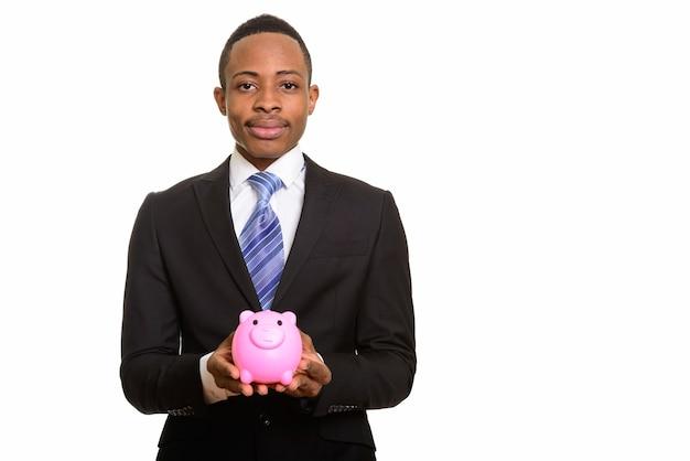 Молодой красивый африканский бизнесмен, держащий копилку