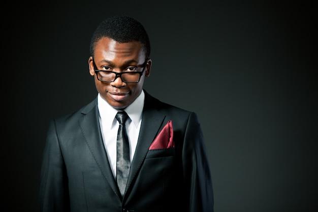灰色の衣装、白いシャツ、ネクタイ、メガネ立って、笑顔で若いハンサムなアフリカの実業家