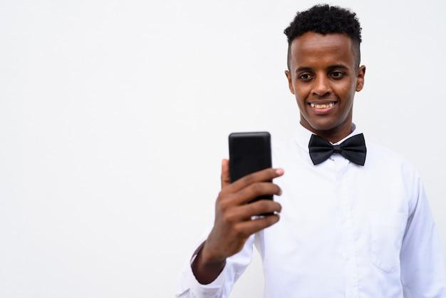 白い背景に、携帯電話を使用して若いハンサムなアフリカの実業家