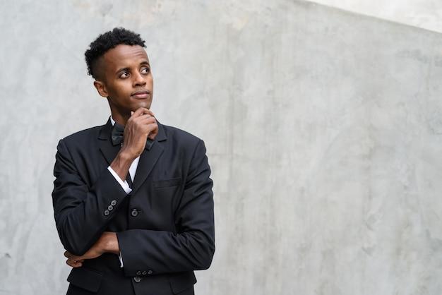 コンクリートに対してスーツを着ている若いハンサムなアフリカの実業家