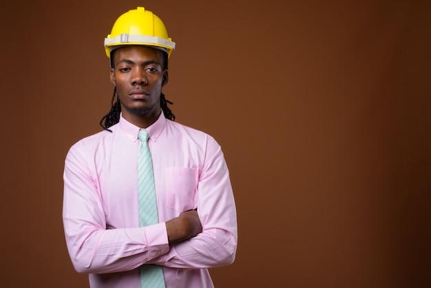 茶色の背景にヘルメットを持つ若いハンサムなアフリカの実業家