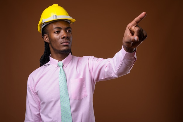 Young handsome african businessman with hardhat against brown background