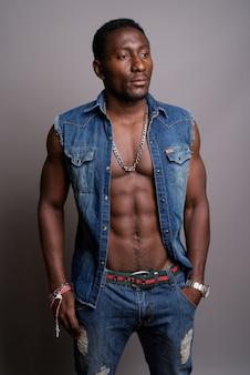 Молодой красивый африканский мужчина на сером фоне