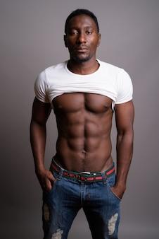 灰色の背景に若いハンサムなアフリカ人