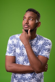 Young handsome african man against green background