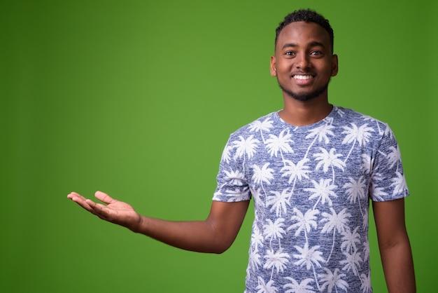緑の壁に対して若いハンサムなアフリカ人