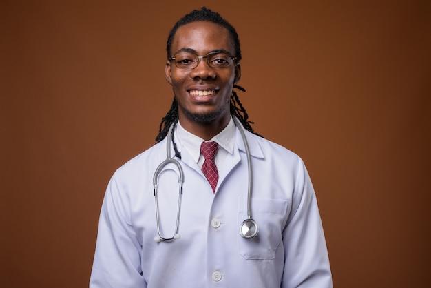 茶色の背景の若いハンサムなアフリカ人医師