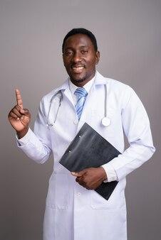 Молодой красивый африканский мужчина-врач на сером фоне