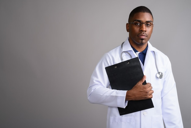 Young handsome african man doctor on gray