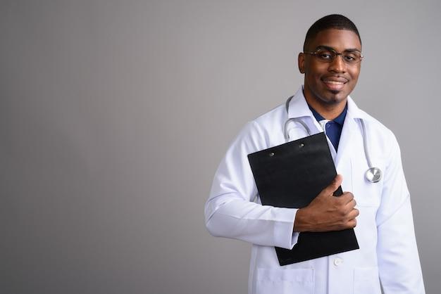 Молодой красивый африканский мужчина-врач на сером