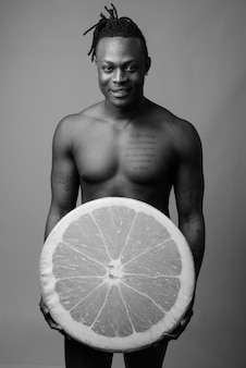 Young handsome african man from kenya shirtless against gray wall in black and white