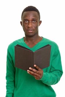 考えながら本を保持している若いハンサムなアフリカ人