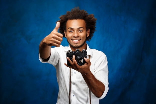 Young handsome african man holding old camera over blue wall.