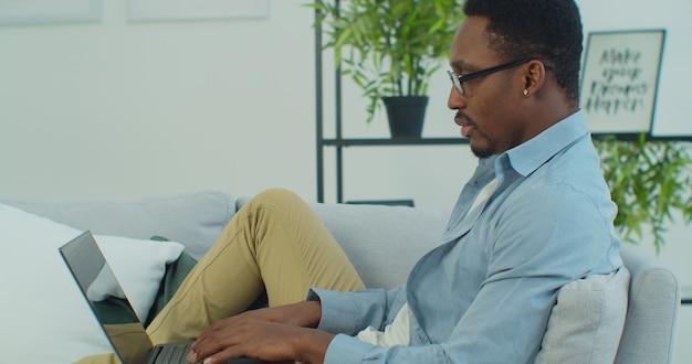 Молодой красивый африканский мужчина в очках использует ноутбук, сидя на диване, работает дома онлайн-технологии интернет