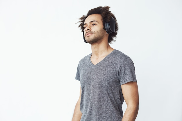 Young handsome african man listening to streaming music in black-the-ear wireless headphones