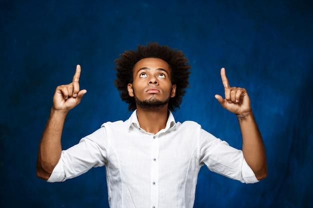 Молодой красивый африканский человек указывая пальцы вверх над голубой стеной.