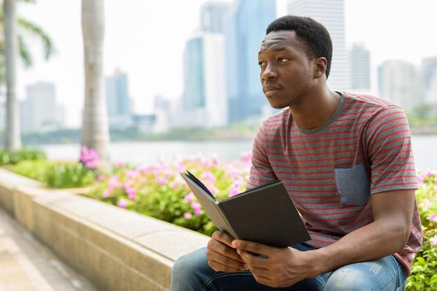 Молодой красивый африканский мужчина отдыхает в парке и читает книгу