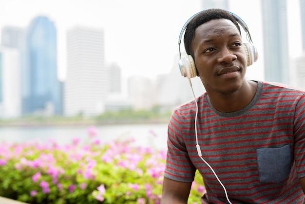 Молодой красивый африканский мужчина сидит в парке во время прослушивания музыки в наушниках